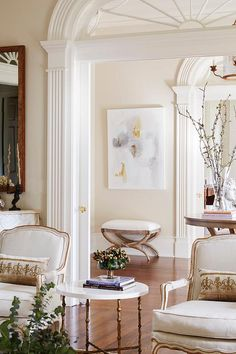 Chic foyer boasts a gold and gray abstract art piece placed over a French stool.