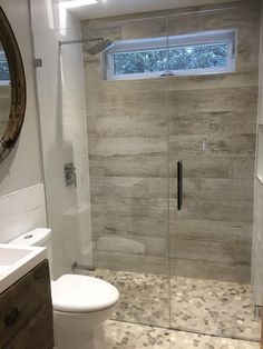Top-Notch Renos - Cottage bathroom with barn board tile wall, mosaic pebble tile heated floor. glass shower doors.
