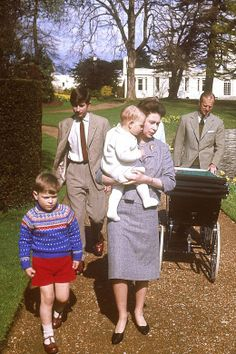 Queen Elizabeth II, wearing black pumps, and her family go for a leisurely stroll around the Lake at Frogmore in