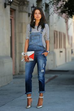Shop this look for $136:  http://lookastic.com/women/looks/overalls-and-longsleeve-shirt-and-statement-necklace-and-statement-earrings-and-clutch-and-heels/1127  — Navy Denim Overalls  — White and Navy Horizontal Striped Longsleeve Shirt  — Silver Statement Necklace  — Silver Statement Earrings  — Multi colored Leather Clutch  — Silver Heels