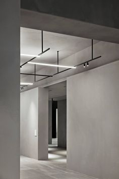 Flos Stand | Vincent Van Duysen | A stand for the Light and Building Fair designed to look like a concrete area full of clean lines. This provides the perfect canvas to display the Flos lighting collection that is minimal and concise using illumination and simple black frames.
