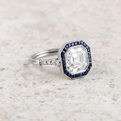 A stunning Asscher cut diamond and Sapphire Ring.  The ring features a very lively 3.13 carat Asscher cut diamond.