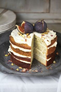 frosted poppy seed cake with frosting topped with pistachios and ripe figs!