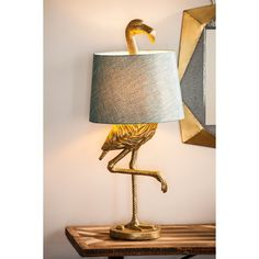 """Brighten up your space with this Fairlee Flamingo 31.89"""" Table Lamp. The lamp is designed to look like a faux gold antique bronze flamingo whose head is poking up from the blue lampshade. Made of polyresin. The lamp has electronic parts with a 65"""" cord and includes a 13 watt bulb."""