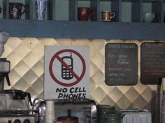 """The """"No Cell Phones"""" sign that Lorelai ALWAYS ignores until Luke yells at her...even when they're dating."""