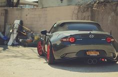 Miata with red rims and pipes