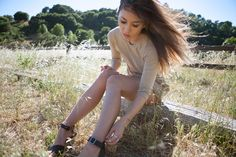 Hair blowing in the wind, in a big grassy field