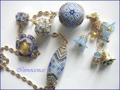 Un sautoir avec les superbes créations de Fabie95(la fabinette en perle centrale),une Olivka de la boutique charlotte avec le meme dessin,une Treya de Pencio avec des toupies Swaro bleues et or,une Pétalis de rubis 63(trop belle avec un cabochon central...