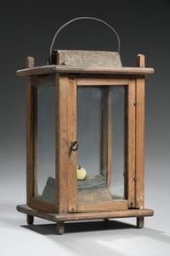 American, early century, in walnut. The pinned frame holding four glass panes, a sheet iron ventilator and what appears to be a period wooden candleholder; in a natural finish;