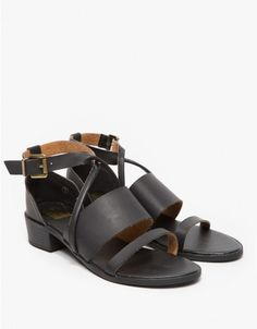 Black faux leather open-toe sandals with crossover strap styling and a stacked heel. Features ankle buckle closure, two straps and front crossover straps.  • Faux leather open-toe sandals • Crossover strap styling • Two straps • Ankle buckle closure