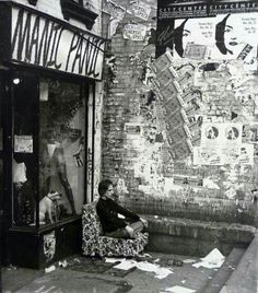 1977 man in meditation outside boutique, Manic Panic on St. Marks Place. Opened by 2 sisters, was the first punk style boutique.  The sisters were singers in the original Blondie line up.  Some history in comments. Victor George Maracol, photog. Bowery Boys.
