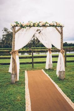 Rustic ceremony altar idea - wooden altar with white fabric draping, burlap bows and flowers {Darin Crofton Photography}