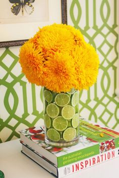 Organic design: Fresh, loud, sunny yellow flowers with limes in vase. Inspired by the Lorax maybe?