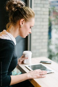 Young business woman using technology sitting at cafe by Wave | Stocksy United