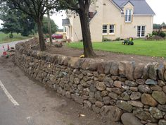 Free-standing wall made from field stone taken from an old and tumbledown dry stone wall.