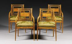 Yes Please! A set of four Regency ebony strung satinwood armchairs early 19th century the backs with entre-lac pierced ornament and a central splat, with down swept arms and caned seats with squab cushions, on square tapering legs