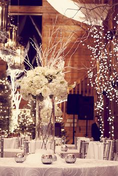 hydrangeas, roses, calla lilies, ranunculus, silver brunia berries and tall birch branches with twinkling lights and crystal strands hanging from branches