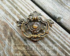 ⌘ This listing is for (1) ONE Pull. ⌘ Measures Approx 2 D | Center Boring ⌘ Mounting Hardware NOT Included ⌘Hardware has a 3-5 Day Processing Time*. Keeler Brass Co Period drawer pulls are a smaller version of our popular larger version. Intricate details & craftsmanship make these pulls absolutely stunning. Gives any piece of furniture or decor a regal, baroque feel with gorgeous antique hardware by Keeler Brass Company, a leader in brass constructed hardware. Antique ribbon ties their leaf…