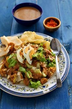 GADO-GADO. ( Indonesiana quick, easy, healthy Salad which consists mostly of boiled or blanched Veggies, tofu, tempeh, green beens, eggs and leafy stuff and accompanied by a sweet and spicy peanut dressing ).