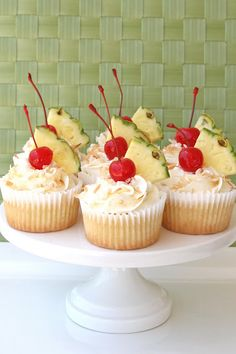 Pina Colada Cupcake with pineapple in the cupcake, topped with a cream cheese coconut icing, toasted coconut, a fresh wedge of pineapple and a cherry on top.  So good