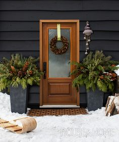 Two tall urns filled with fresh evergreen boughs and a pinecone-covered wreath add rustic warmth to the charcoal paneling of this home in Creemore, Ontario. | Photographer: Donna Griffith | Designer: Grace Castaneda