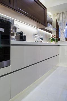 Μοντέρνα κουζίνα με ντουλάπια από λευκό ακρυλικό με ενσωματωμένες χούφτες στο…