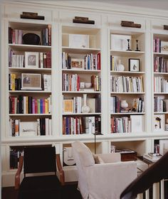 chic brass library lights. collections of white ceramic vases. a few other black + white objects.