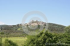 A Medieval tuscan village located on the top of the hill surrounded with olive groves and blue sky in the bakground