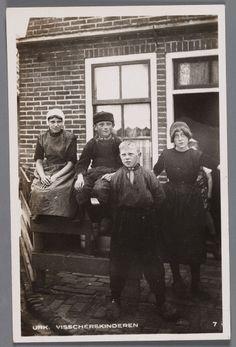 Vier kinderen in eenvoudig dracht, twee jongens en twee meisjes staand tegen of zittend op een hekje voor een woning. 1910-1930 #Urk