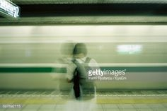 Foto stock : Rear View Of Woman Standing On Railroad Station Against Moving Train