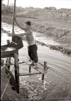 Farmer irrigating field with counter-balanced water lifting device (water scoop) in the countryside near Tientsin, spring 1946. Harold Giedt Photographs. Old China Hands Archives.