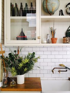 subway tile, wood counter, farmhouse sink (weird accessories on the shelves for a kitchen though.  who needs a globe in the kitchen...?)