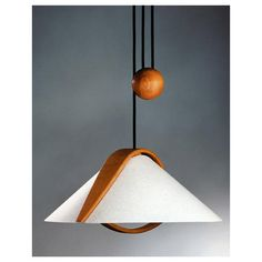 A lovely and simple design made from handcrafted alder wood, including a wood canopy, and a polycarbonate translucent shade that suggests the appearance of fine parchment paper. This Asian influenced Contemporary functional pull-down pendant comes with a black cord that has a maximum drop from the ceiling of 8 feet.