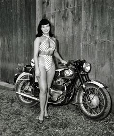 Bettie Page posing next to a BSA motorcycle