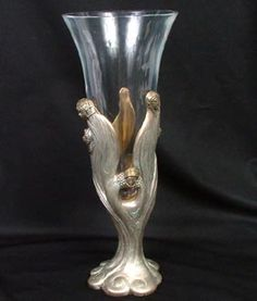 """Erte """"Visage de Femme"""" (faces of women) Art Deco silvered and gilt bronze withh crystal trumpet vase insert. This work is Erte's homage to the complex woman of today, her many faces, her beauty."""