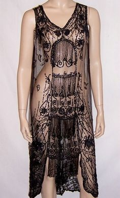This is a striking 1920s vintage, black beaded and sequined dress on fine black net.  The dress has a series of rows of black beaded fringe down the center panel of the dress.  It has a V-neckline in both the front and the back, each which has been embellished with lovely sequined floral motifs.