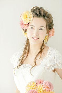 パステルカラーのヘッドコサージュが主役の華やかなヘアアレンジ。こめかみのあたりに大きなコサージュを飾り、花嫁のフレッシュで生き生きした表情を...