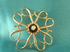 Classy flower with diamond in center of 10K yellow gold pin  $186.50
