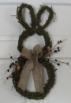 Easter Bunny wreath made from moss covered grapevine and decorated with artificial berries and a natural burlap bow. on Etsy, $40.00