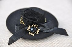 Black Tiny Top Hat, black top hat black mini hat, tea party hat, Black Fascinator gothic top hat mad hatter hat, steampunk top hat festival  This one-of-a-kind Tiny Top Hat It is hand-made in my studio  This cute little hat is covered in a black fabric. TDecorated satin ribbon, bronze chain, lace, glass beads This hair clip measures approximately 0.75 tall and 3 wide.  Clip underneath - flat crocodile clip  Every hat in my shop is unique and hand made from top to bottom using my own pattern…