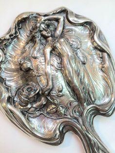 An Art Nouveau beveled handheld vanity mirror.