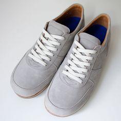 快適に歩く道具としての靴。日常着としてのレザースニーカー。少しタイト目の履き心地は、経年により足に馴染む繋ぎ目のない一枚革のアッパーパターン。履きこむほどに自分の足の形に沿っていきます。一点一点切削により成形されるソールは、反発しすぎない街歩きに最適な程よい硬度設計に。装飾を削いだ見た目はどんな服装にも合わせやすく、それでいてアクセントにもなってくれます。丸いシルエットに、ドレッシーな革の表情が品良く映える、限定のホワイトスムースレザーモデルです。
