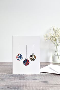 Liberty fabric sewn Christmas card. Pretty Liberty fabric is stitched directly onto the card to create a lovely embroidered Christmas bauble card. A thoughtful handmade card to send to a special person at Christmas time. #libertyfabric #christmascard #christmasbaublecard #sewnchristmascard #stitchedchristmascard #embroideredchristmascard #sewncard #embroideredcard #stitchgalore Elegant Christmas, Christmas Baubles, Christmas Decorations, Christmas Cards To Make, Christmas Time, Freehand Machine Embroidery, Fabric Cards, Liberty Fabric, Card Envelopes
