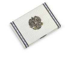 A Russian jewelled gold and guilloché enamel cigarette-case Marked Britsyn, St Petersburg, 1908-1917 Rectangular, the body enamelled in translucent oyster white over a waved ground, the hinged cover applied with a gold, enamelled and diamond-set Imperial eagle, the ends with white and blue champlevé enamel bands with dot and dash decoration, with rose-diamond thumb-piece, marked inside cover and base 3 7/8 in. (9.8 cm.) long