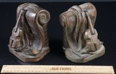 WONDERFUL PAIR OF COMPOSITE BOOKENDS WITH SCROLLING SHEET MUSIC AND STRINGED INSTRUMENT, LOOKS LIKE A VIOLIN. BOOKENDS HAVE FELT FEET AND MEASURE 6 INCHES TALL.