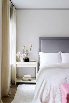 Serene white bedroom with feminine nightstand details