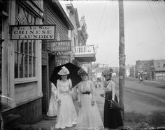 Three women (Jennie Parsons Kelly, left, and Lena Eisenback Post, center, and an unidentified woman on the right) on Main Street in front of a Chinese laundry. They wear elaborate hats and carry parasols (c. 1895). I love how happy they all look - one doesn't see smiles in street photos from this era all that often. It's a wonderful treat. #vintage #Victorian #street_photography #women #fashion