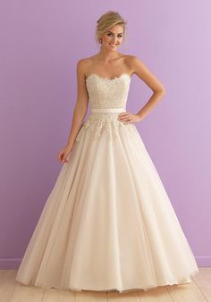 This ballgown is topped by a strapless lace bodice, shaped by a simple satin waistband.