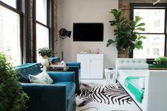 aménagement salon avec fauteuils en bleu canapé droit en blanc et tapis à motif zèbre