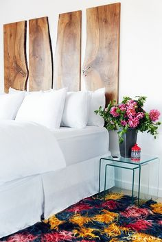 Flowers at bedside of crisp white bed and wood headboard
